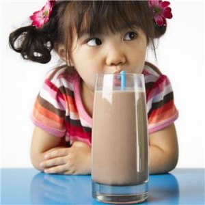 Girl drinking a glass of chocolate milk through a straw
